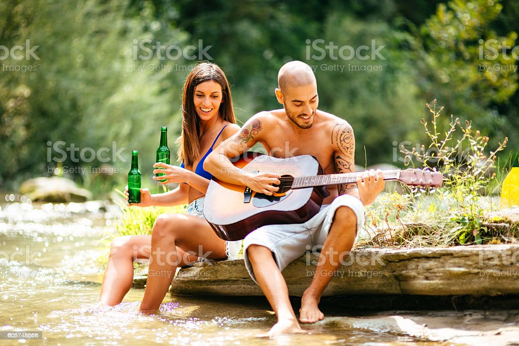 couple flirting on the river playing the guitar stock photo