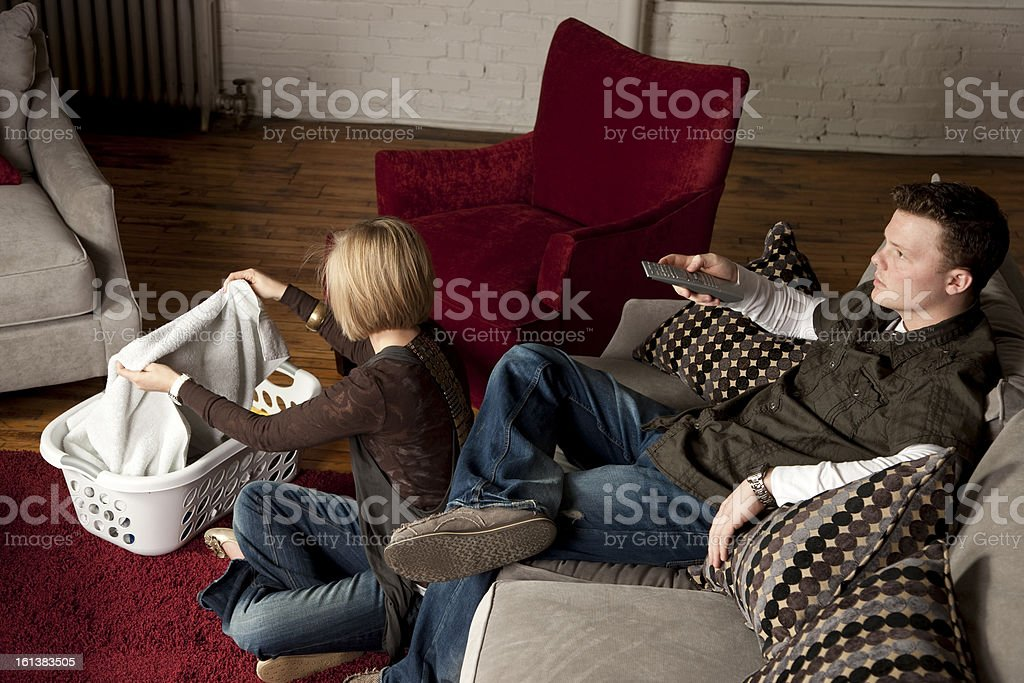 Couple Folds Laundry and Watches Television royalty-free stock photo