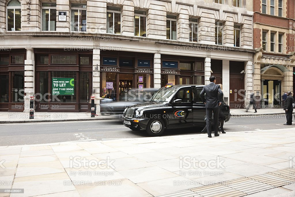 Couple getting into taxi cab in London, UK stock photo