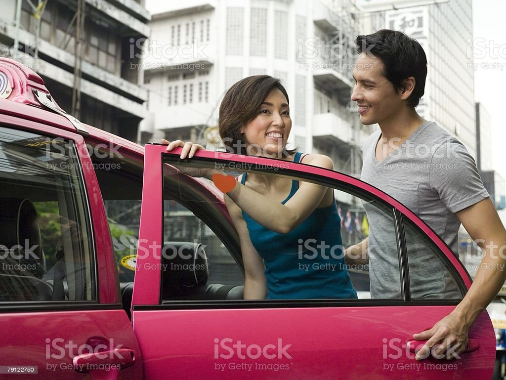 Couple getting into taxi stock photo