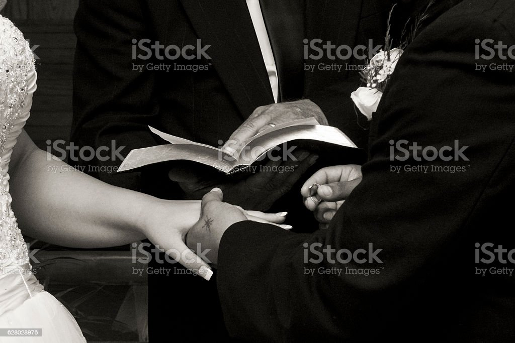 Couple getting married putting rings stock photo