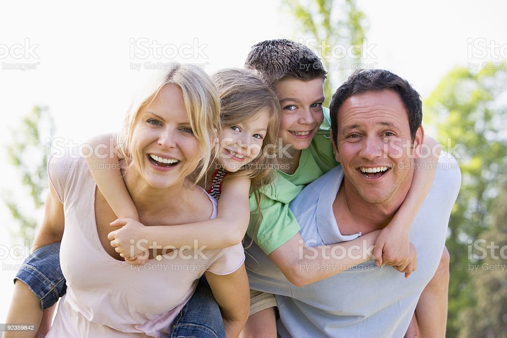Couple giving two young children piggyback rides stock photo