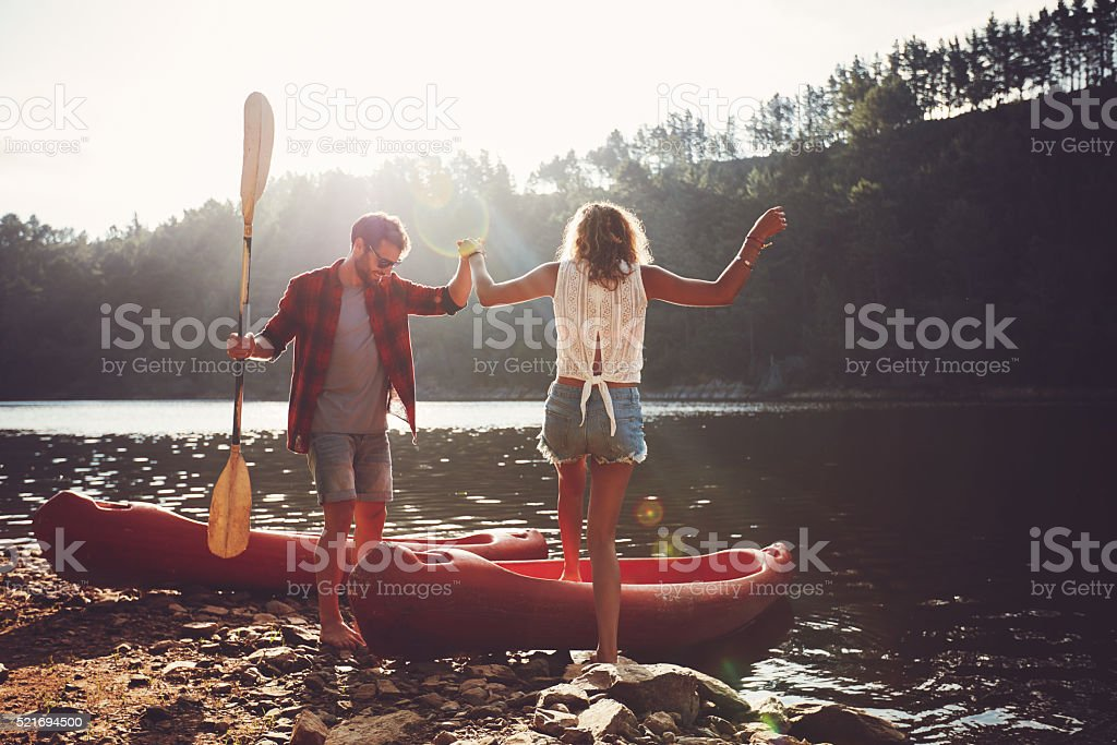 Couple going for a canoe ride in the lake. stock photo
