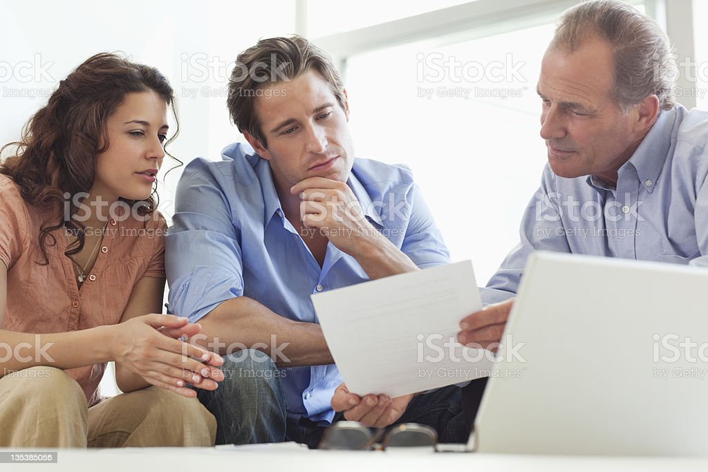 Couple going over paperwork with financial advisor stock photo