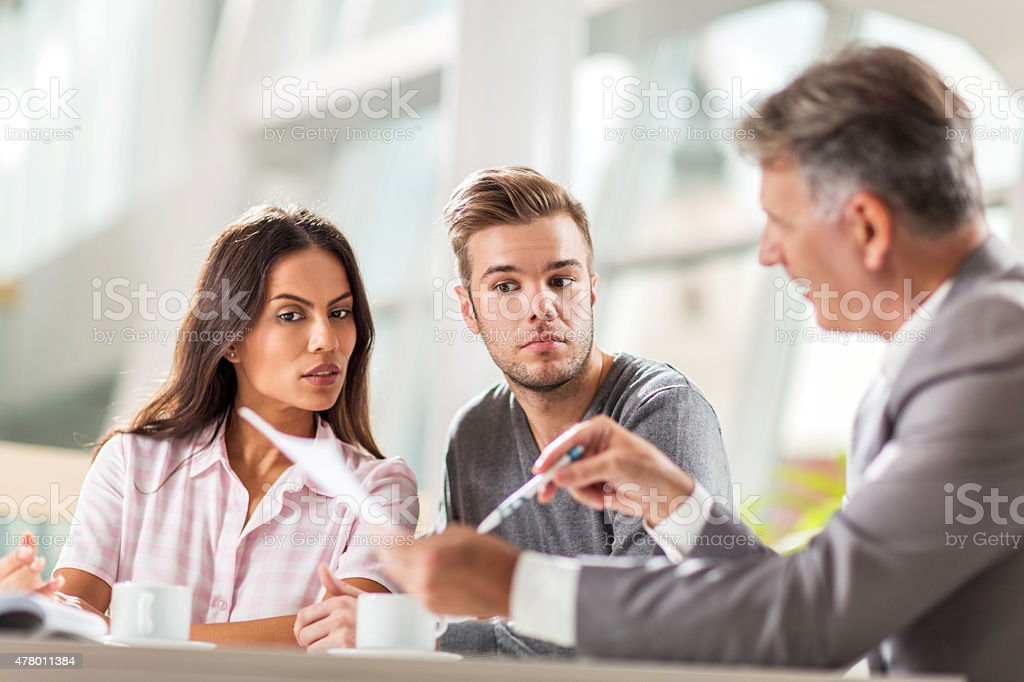 Couple going through paperwork with their real estate agent. stock photo