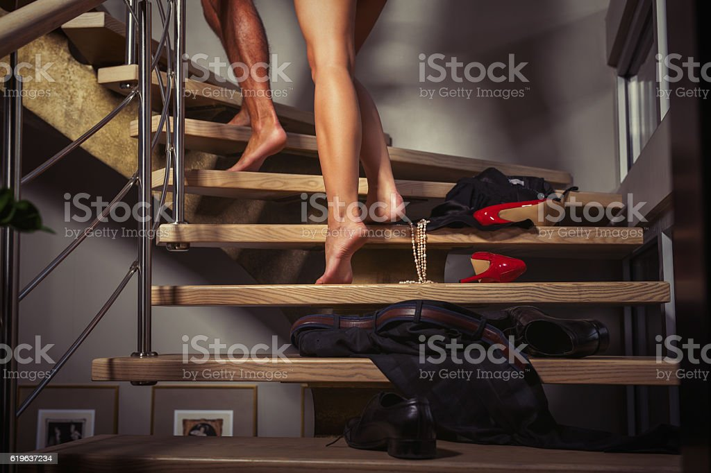 Couple going upstairs to the bedroom stock photo
