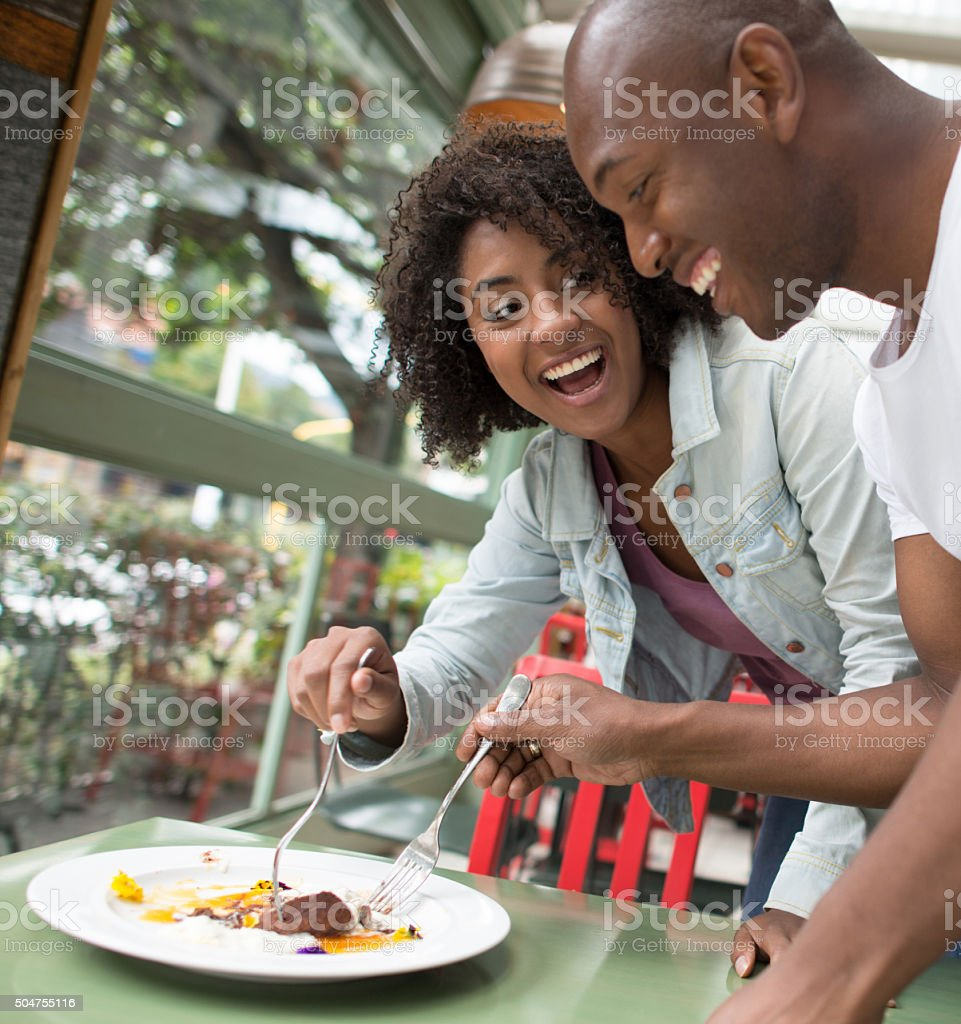 Couple grabbing a bite at a restaurant stock photo