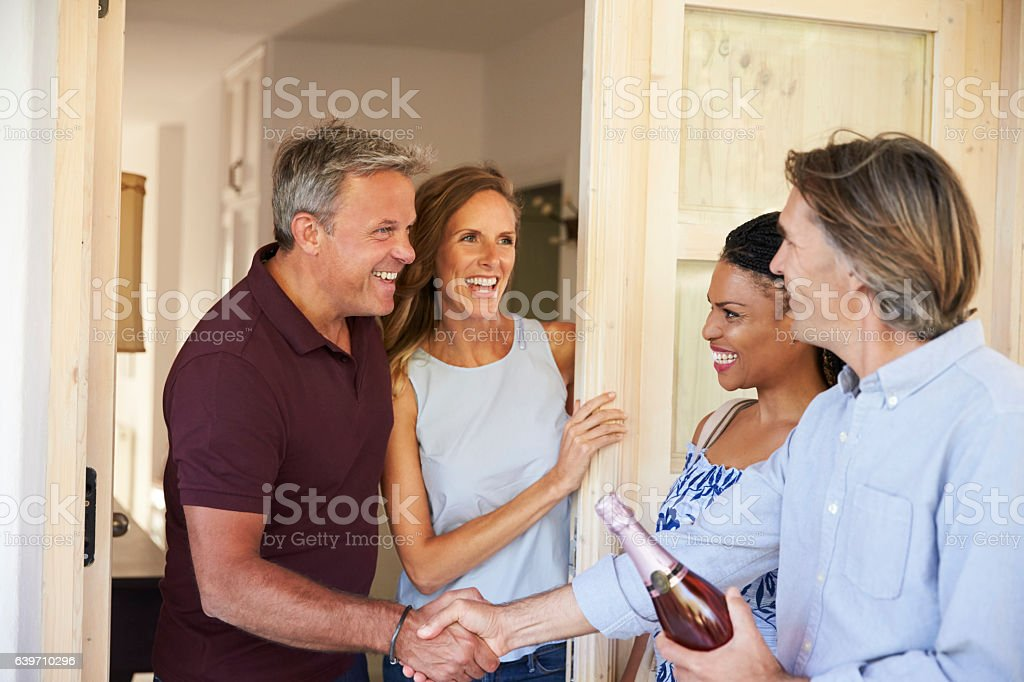 Couple greeting their guests at the door of their home stock photo