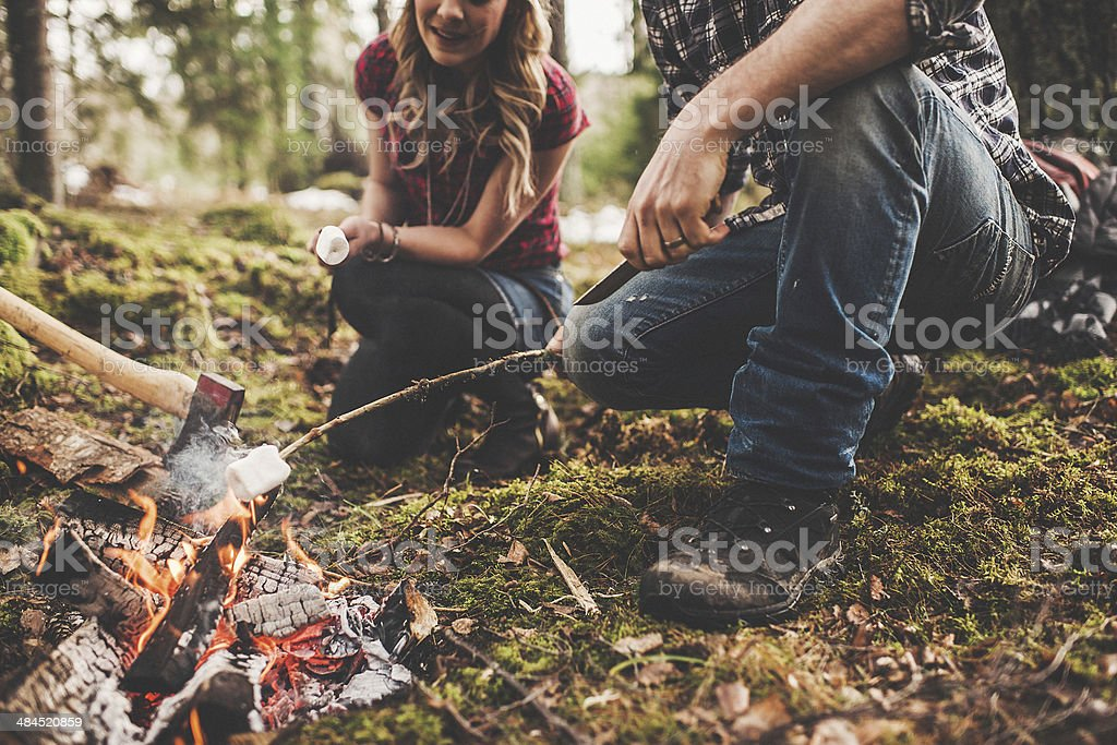 Couple grilling marshmallows by a camp fire stock photo