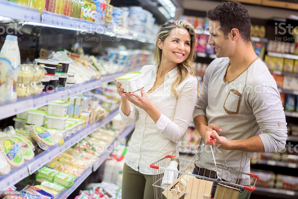 Couple grocery shopping at the food market stock photo