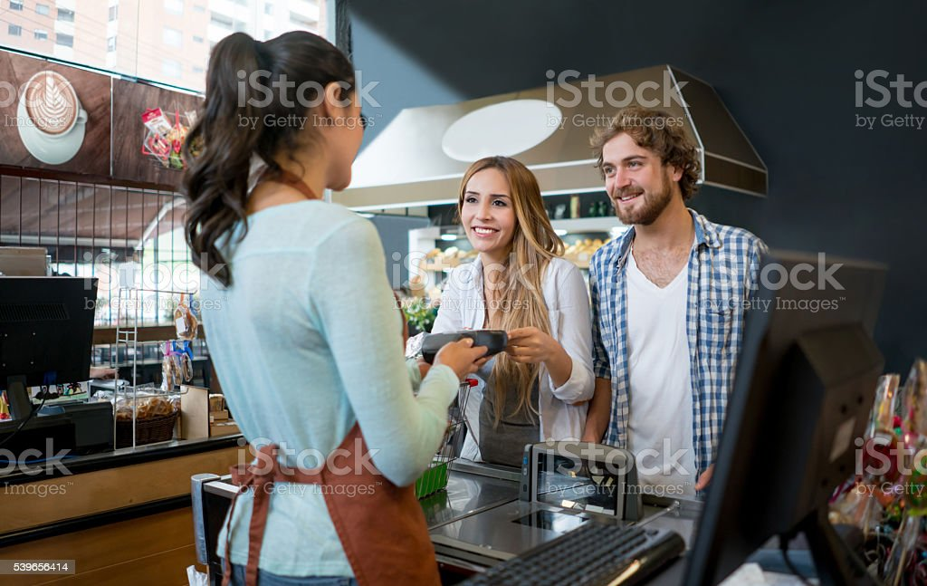 Couple grocery shopping at the supermarket stock photo