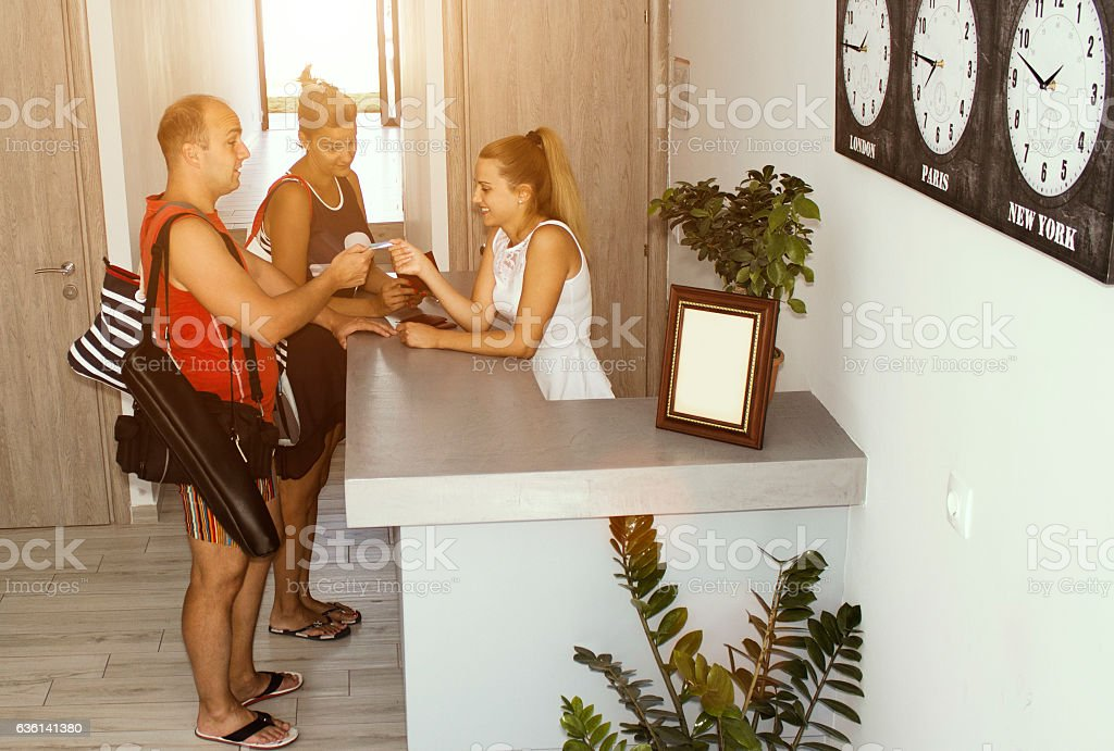Couple handing passports to female hotel receptionist stock photo