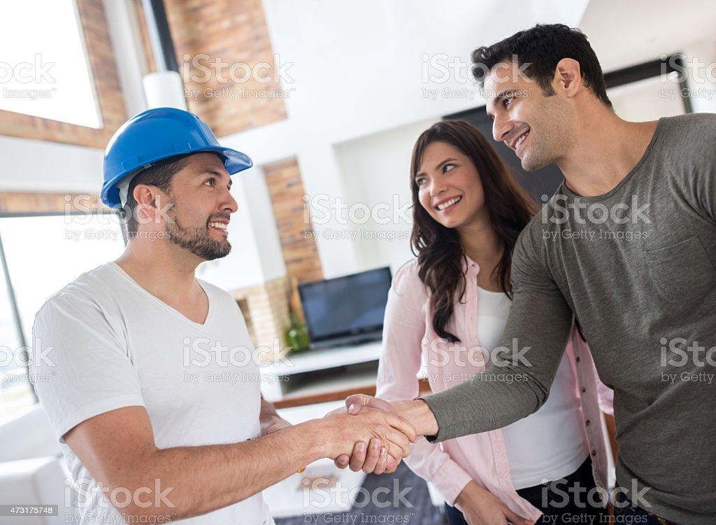 Couple handshaking hand of a handyman stock photo