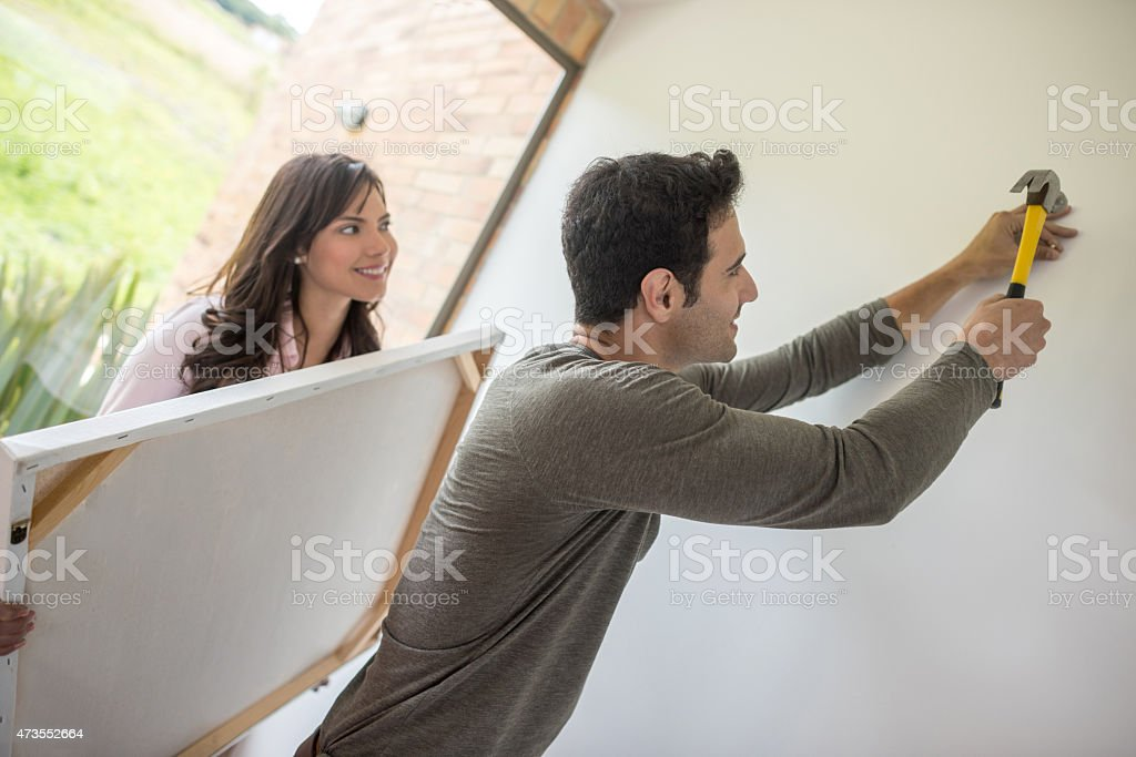 Couple hanging a painting stock photo