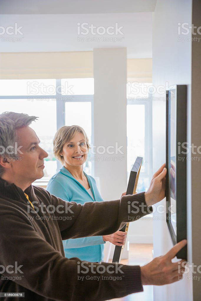 Couple hanging art in house stock photo