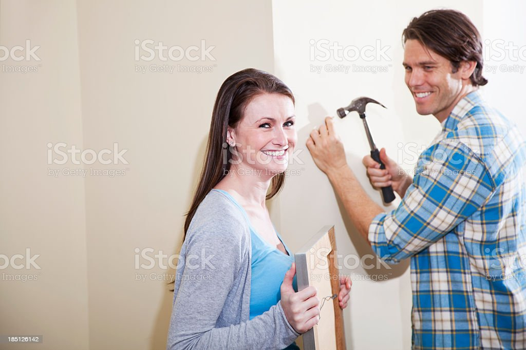 Couple hanging picture on wall royalty-free stock photo