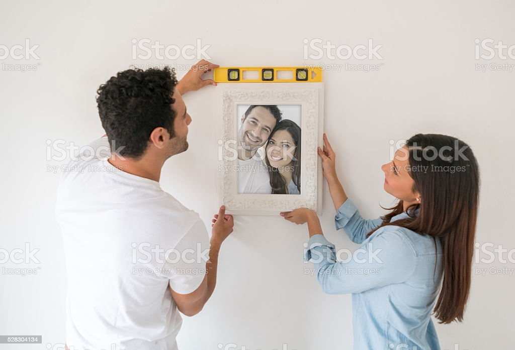 Couple hanging portrait at their new house stock photo