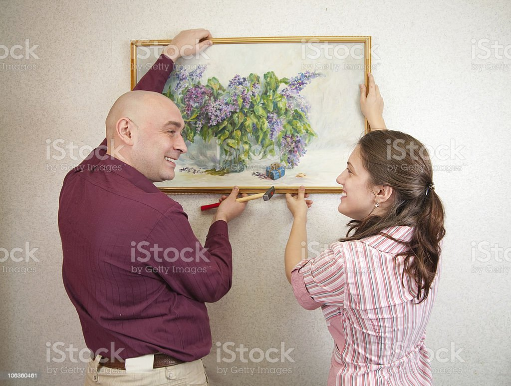 couple hanging up an art picture on their wall royalty-free stock photo