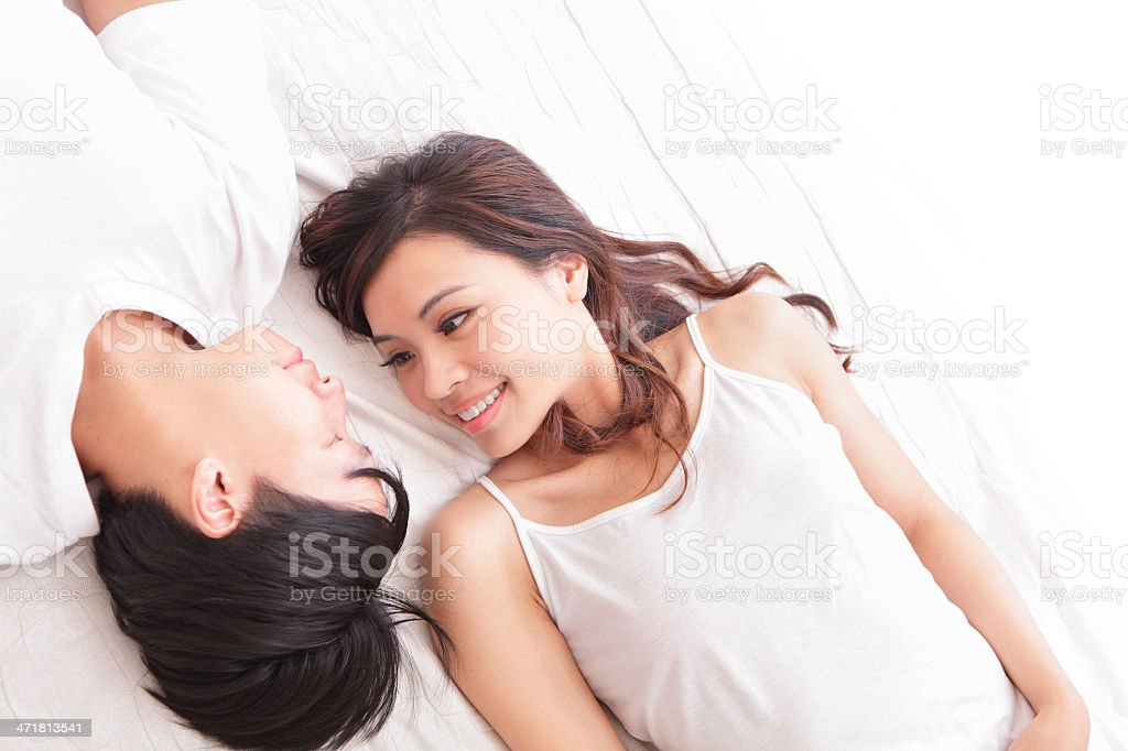 couple happy smile looking to each other in bed stock photo