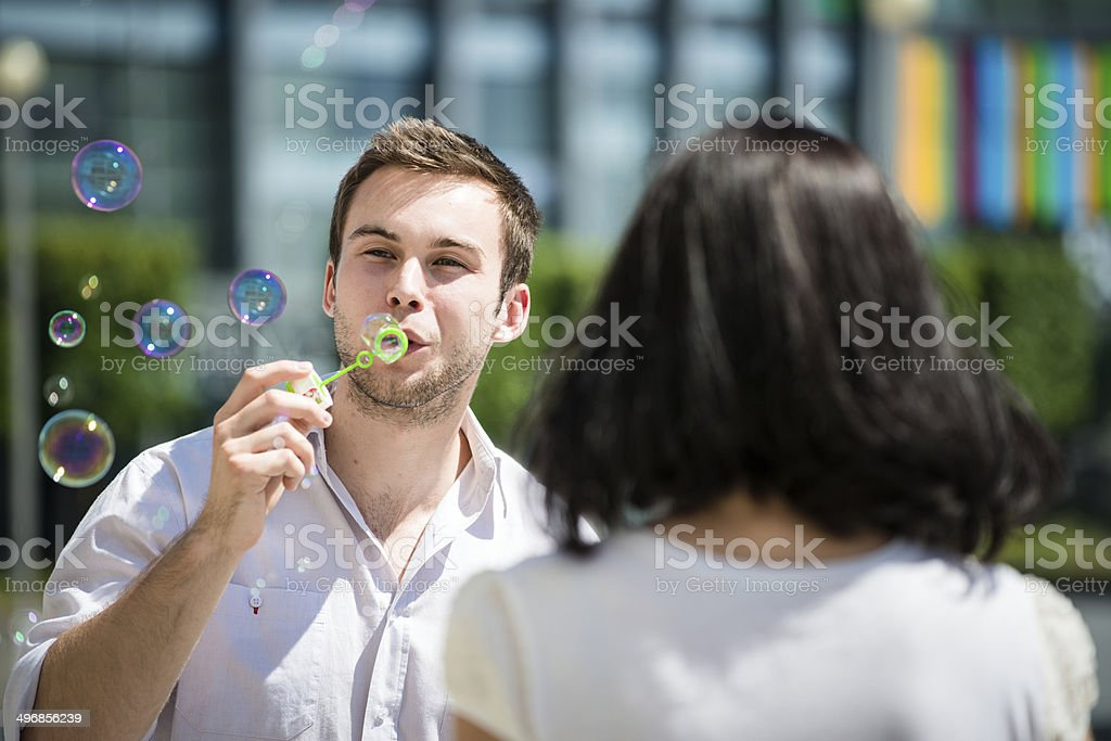 Couple have fun with bubble blower royalty-free stock photo