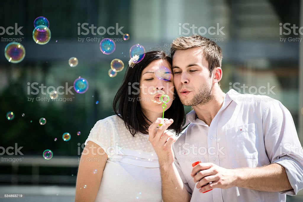 Couple have fun with bubble blower stock photo