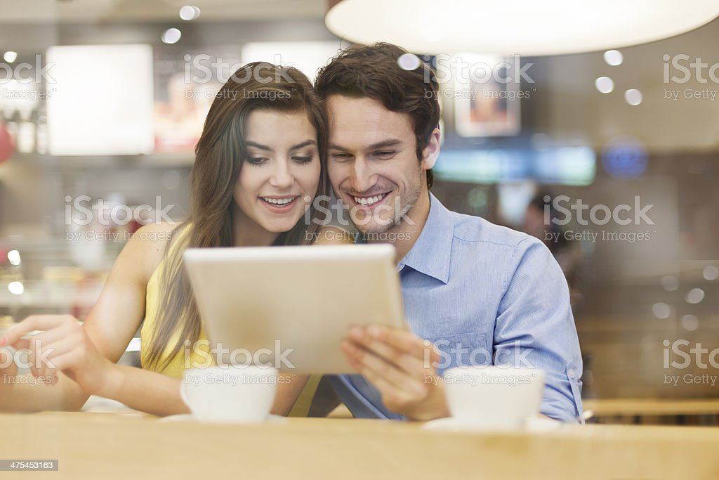 Couple have fun with digital tablet in cafe royalty-free stock photo
