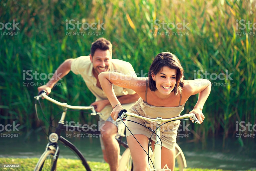 Couple having a bicycles race into the nature stock photo