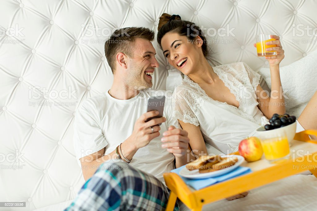 Couple having a breakfast in bed stock photo