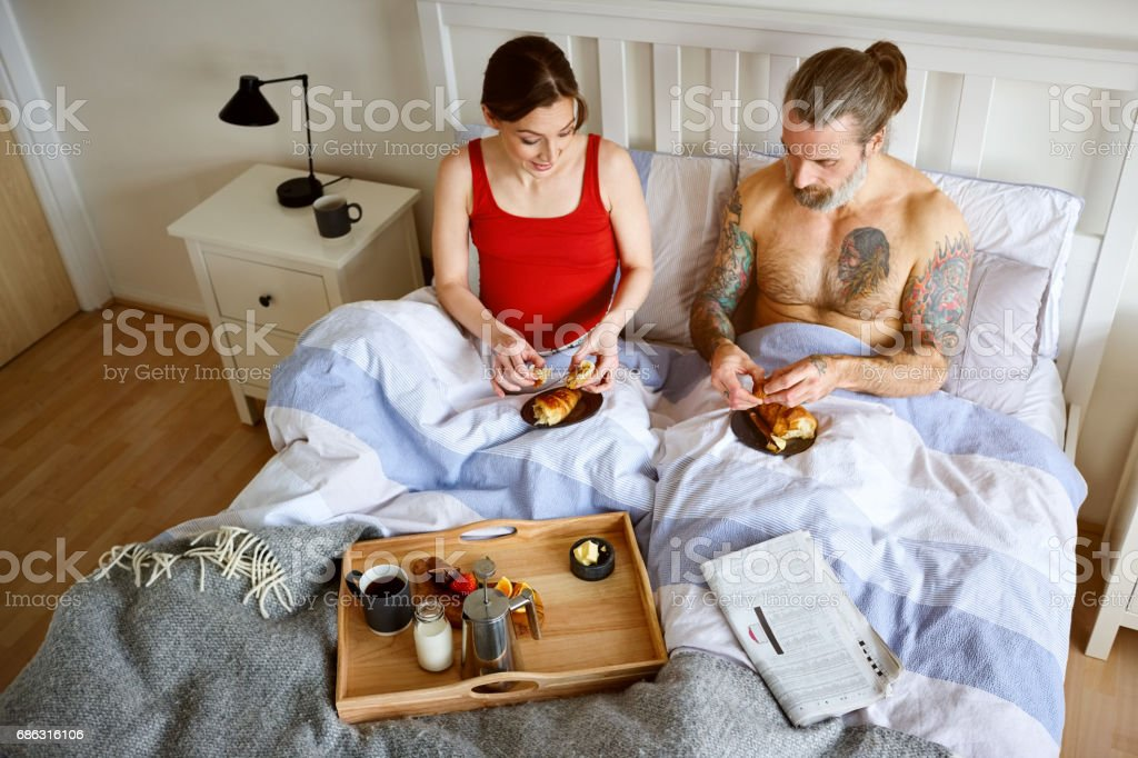 Couple having a breakfast in the bed stock photo