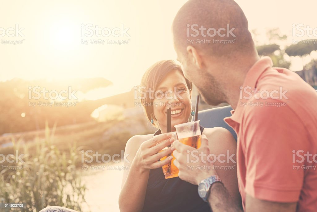 Couple having a cocktail outdoor at sunset stock photo