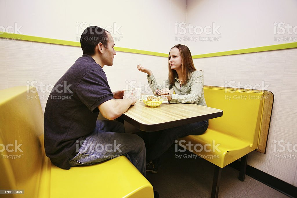 Couple Having a Conversation Over Donuts stock photo