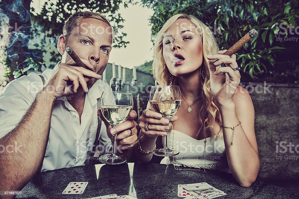 Couple having a drink and smoking cigar royalty-free stock photo