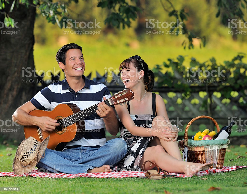 Couple having a picnic in the meadows, playing guitar (XXXL) royalty-free stock photo