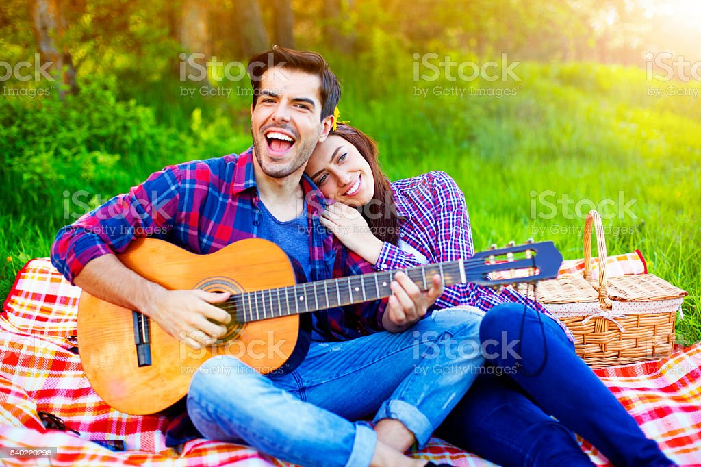 Couple having a picnic in the meadows, playing guitar stock photo