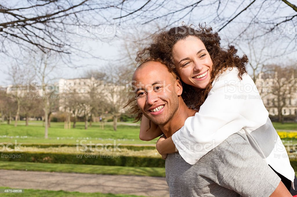 couple having a piggyback in the park royalty-free stock photo