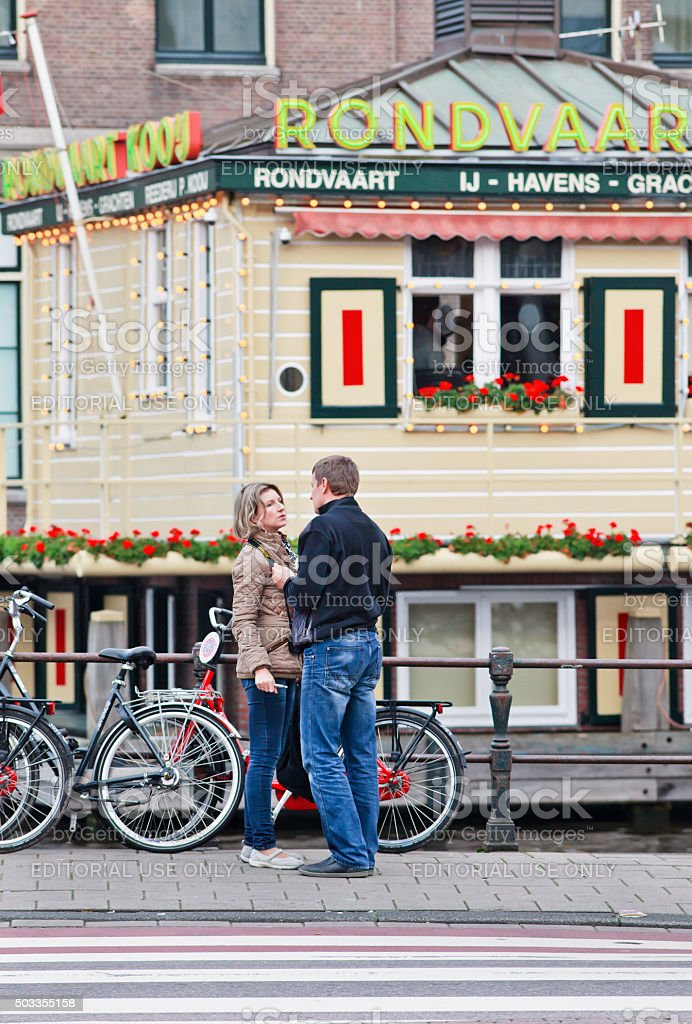 Couple having a romantic moment near tour boat ticket office. stock photo