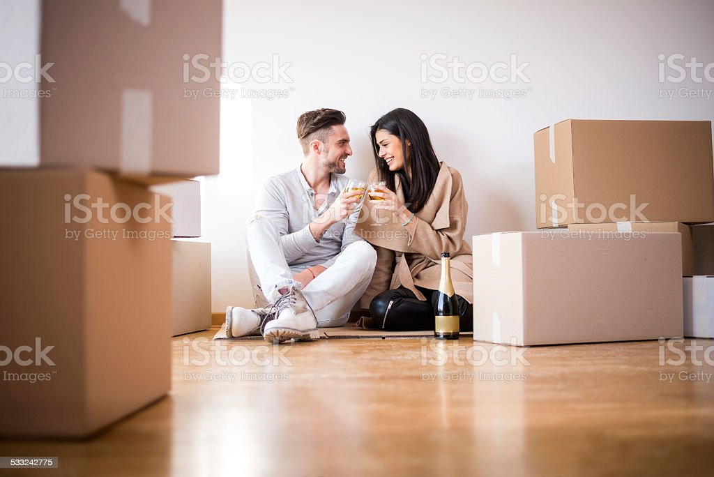 Couple having a toast in new apartment stock photo