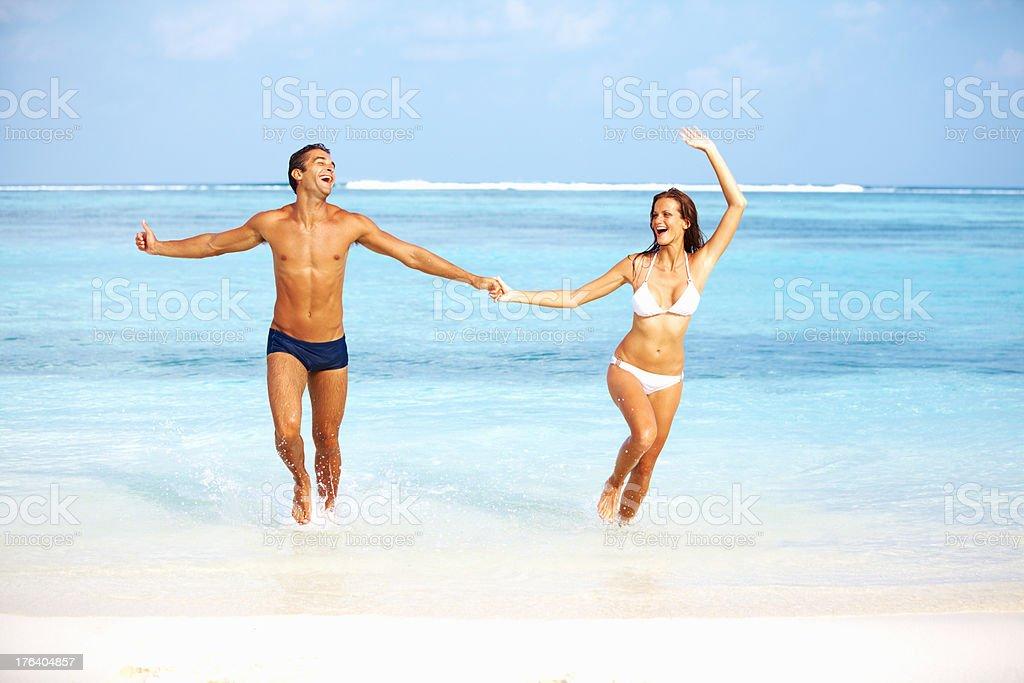 Couple having beach fun stock photo