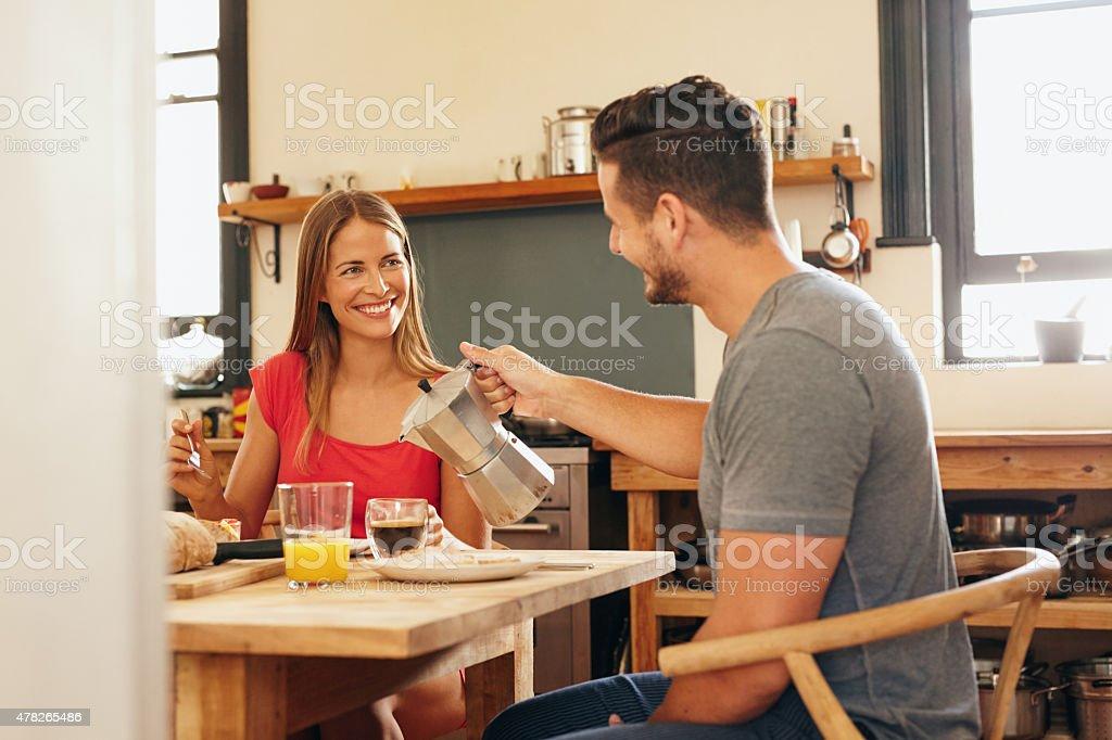 Couple having breakfast, man serving coffee. stock photo