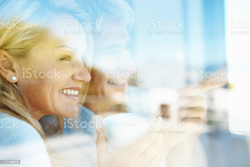 Couple having coffee and looking out the window stock photo