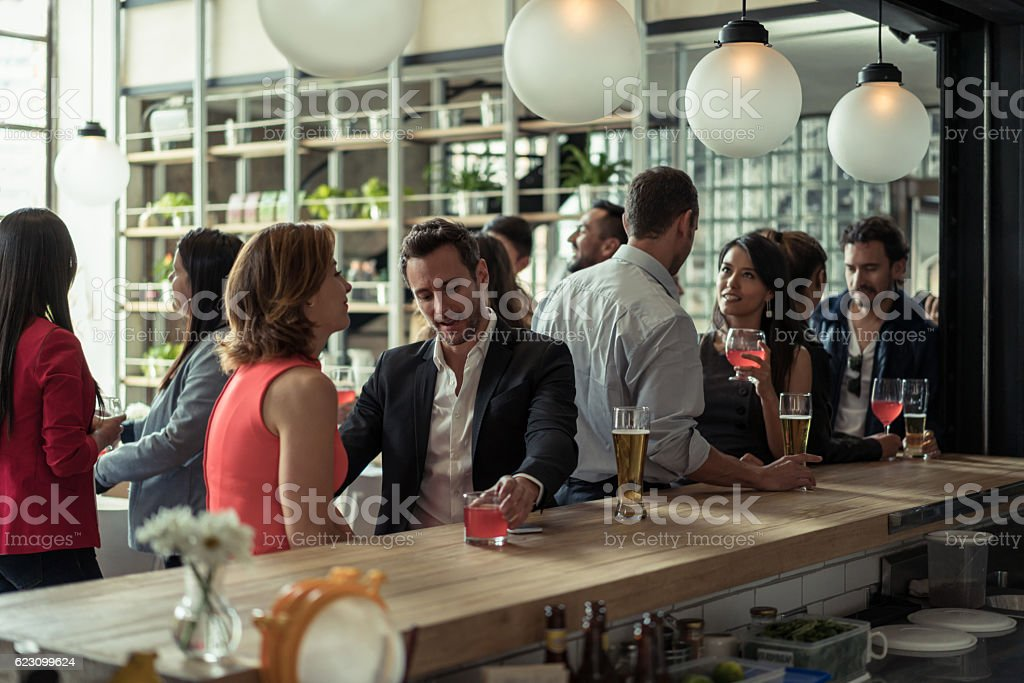 Couple having drinks at a bar stock photo
