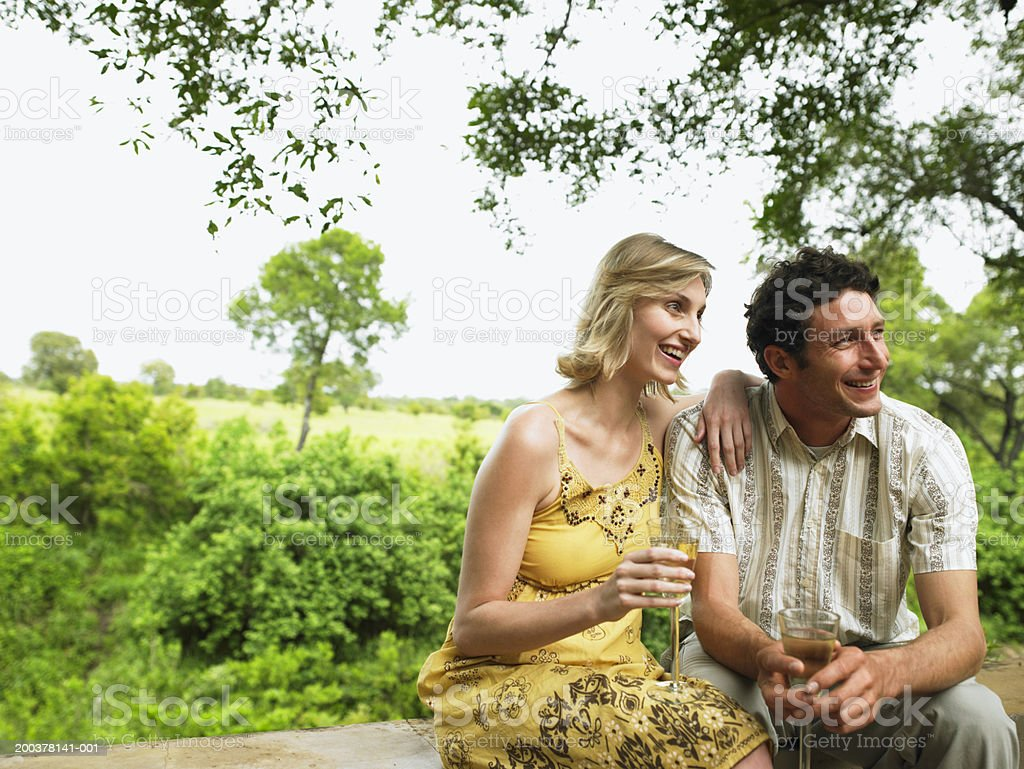 Couple having drinks on terrace, smiling royalty-free stock photo
