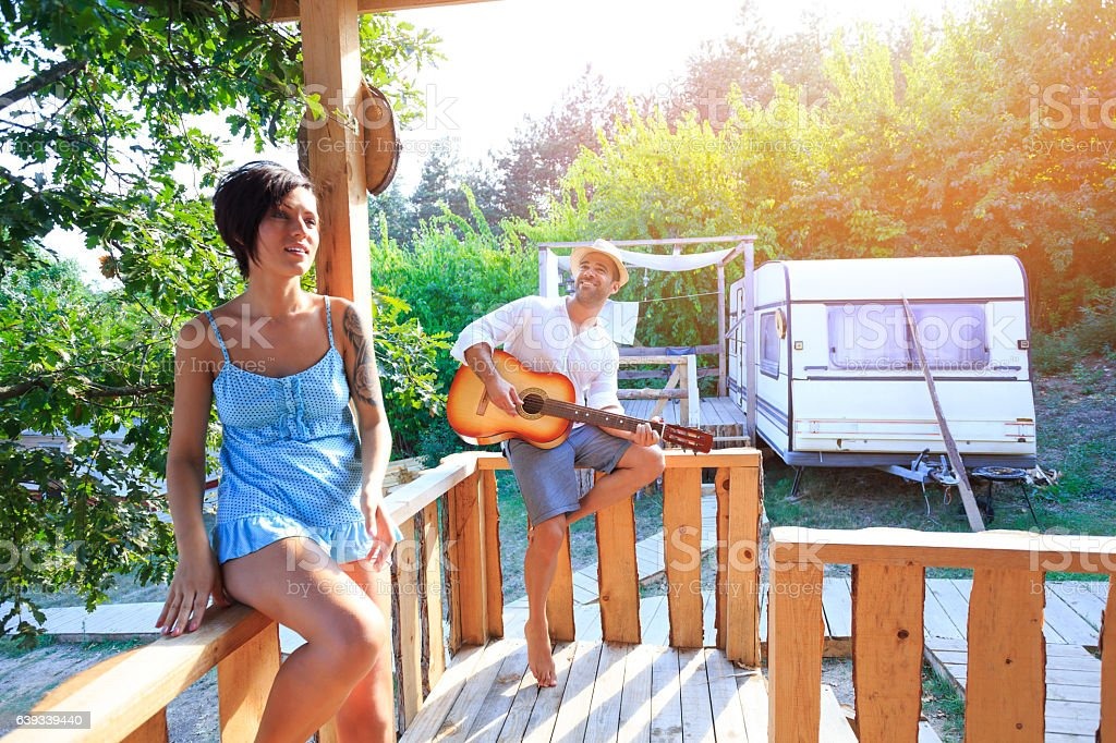 Couple having fun and playing guitar on pavilion stock photo