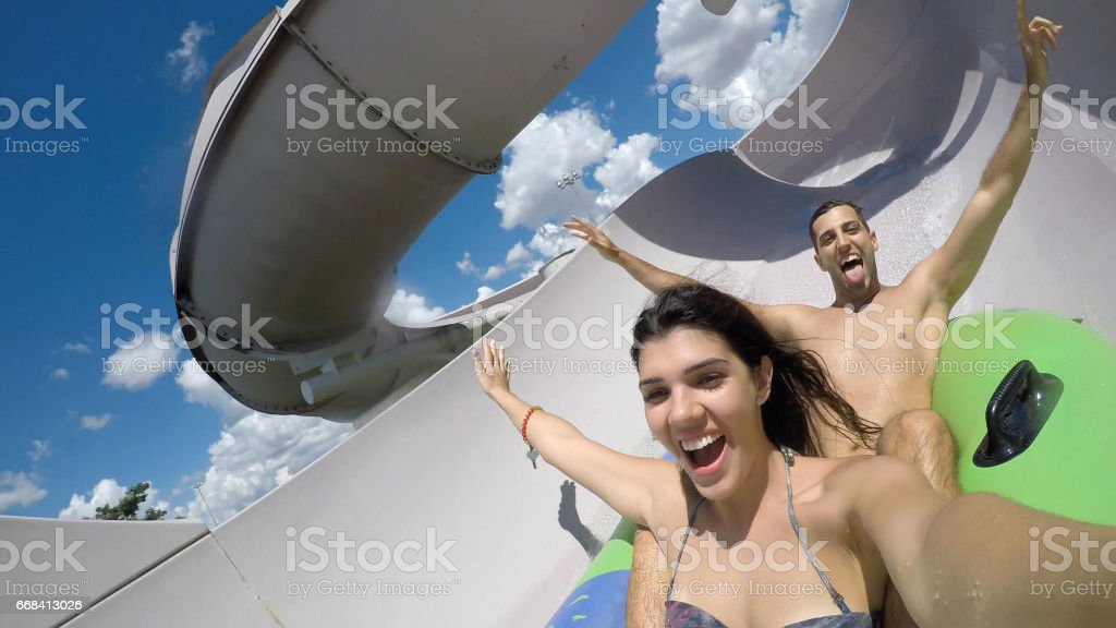 Couple having fun and sliding down in a water slide stock photo