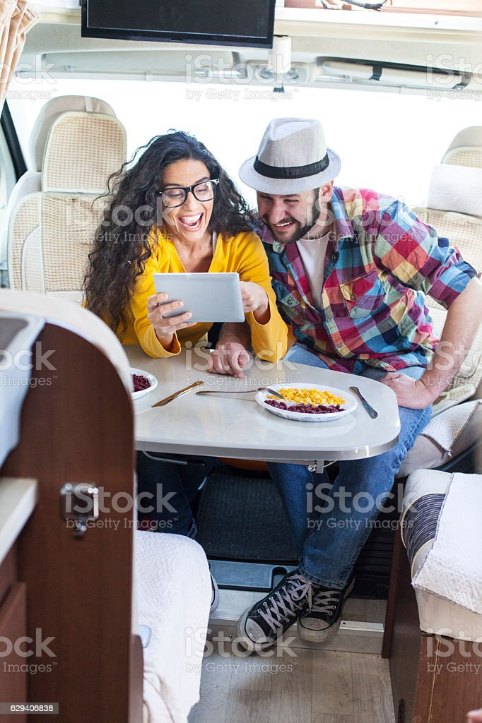 Couple having fun and using digital tablet inside of caravan stock photo