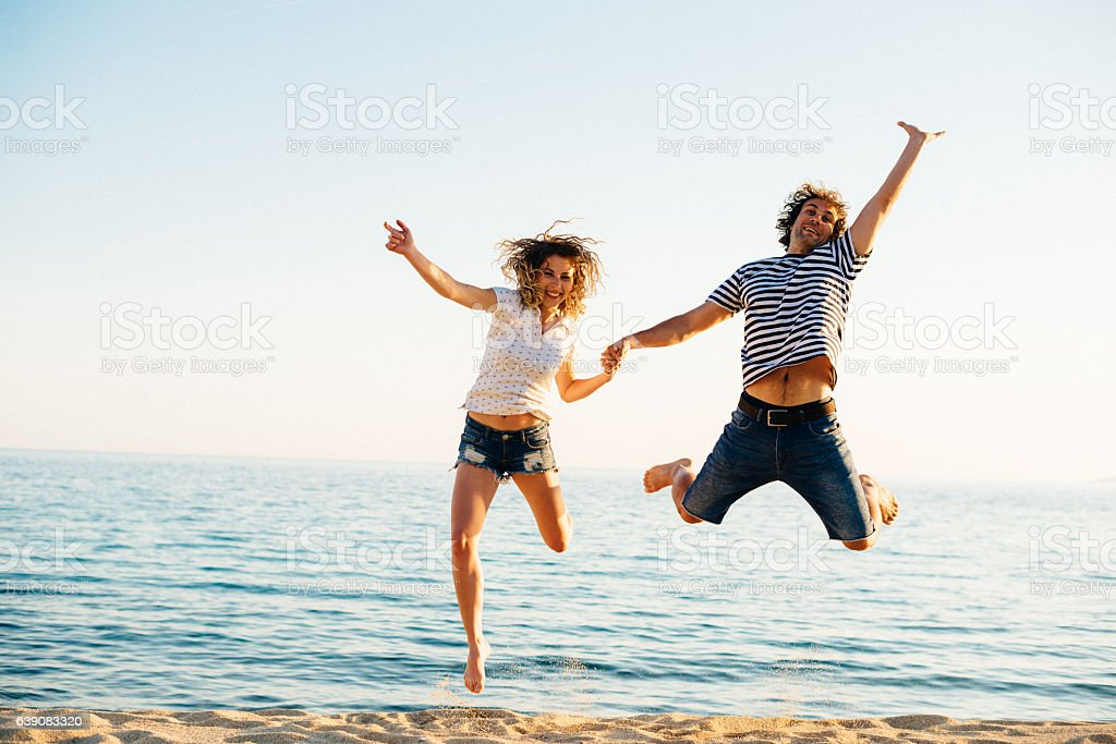 Couple having fun at beach in summer, jumping on sand stock photo