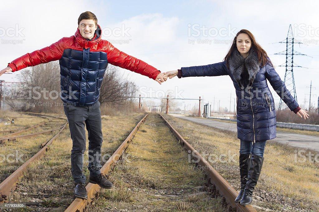 Couple having fun balancing on a railway line stock photo