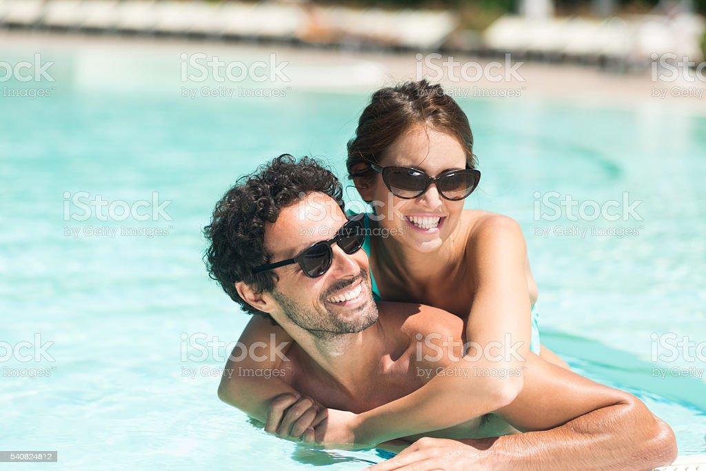 Couple having fun in a pool stock photo