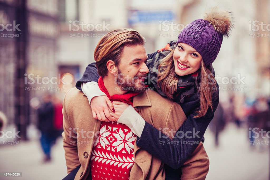 Couple having fun outdoors in winter city. stock photo