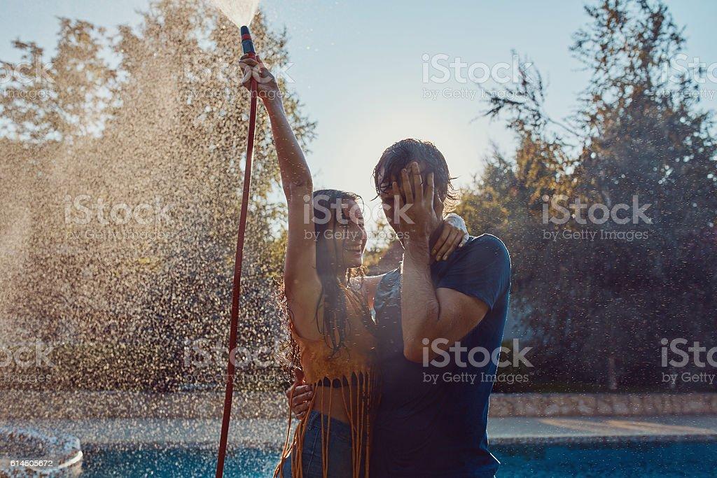 Couple having fun pour each other with garden hose stock photo